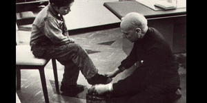 Fr. Pedro Arrupe, S.J, the 28th Superior General of the Society of Jesus, polishes the shoe of a child at Quito, Ecuador